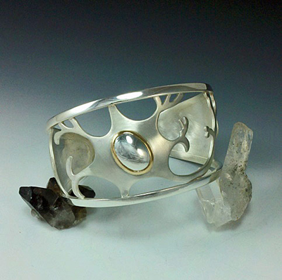 Satin finished silver neuron cuff, accented by polished silver nucleus in 18kt yellow gold bezel. Gorgeous.
