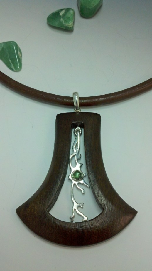 Dancing silver neuron in wooden frame, with blue-green tourmaline nucleus